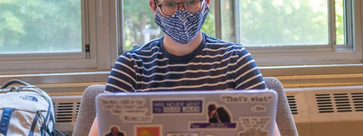 Student using a laptop wearing a mask